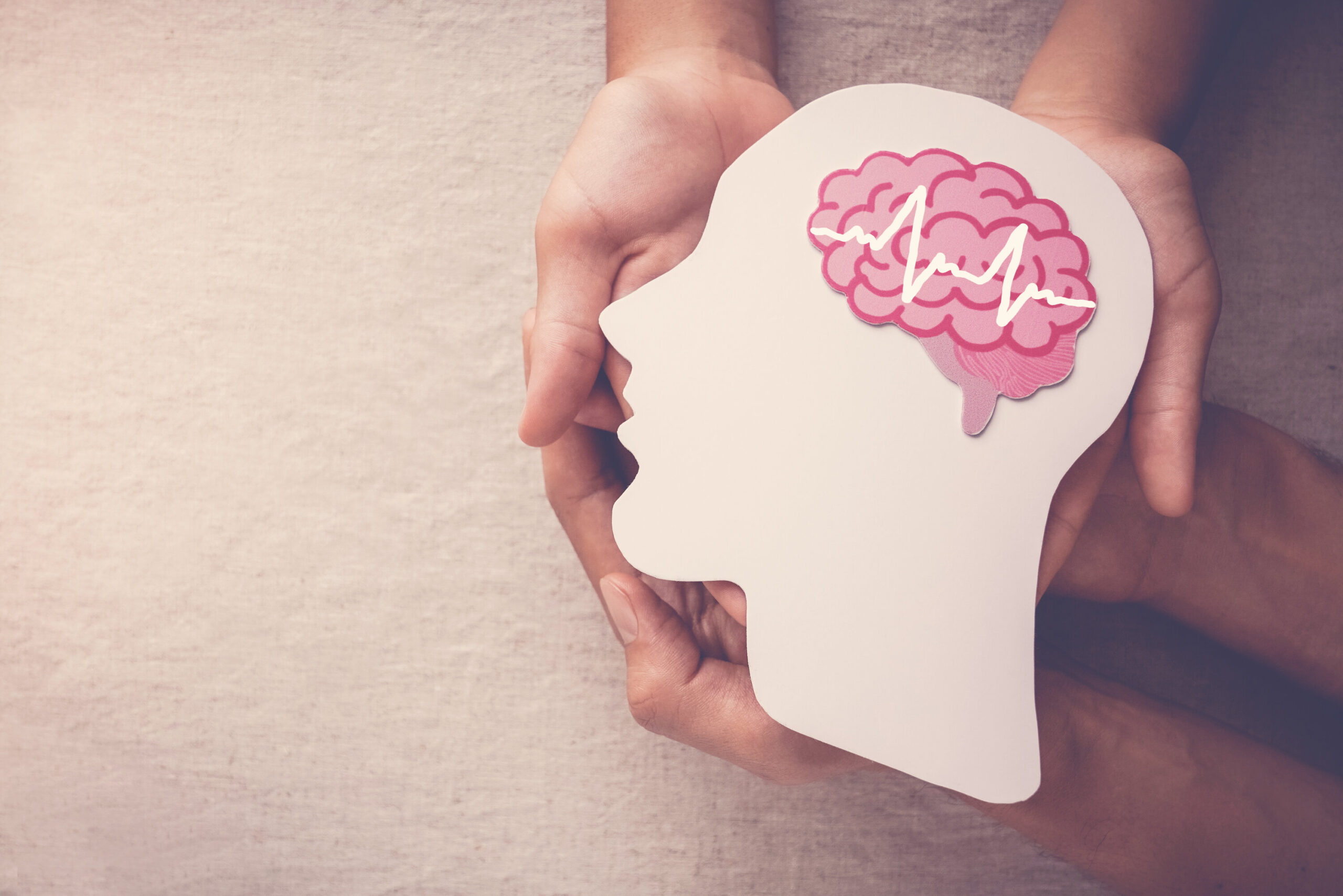 Adult and child hands holding encephalography brain paper cutout